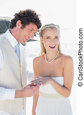 Handsome man placing ring on smiling brides finger at the...