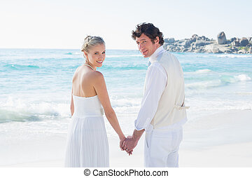 Bride and groom holding hands looking at camera at the beach