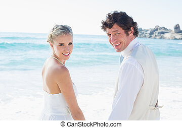 Bride and groom holding hands smiling at the camera at the...