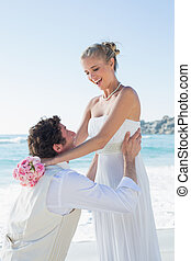 Laughing groom picking up his pretty blonde wife at the...