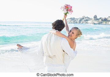 Handsome groom carrying his beautiful laughing wife at the...