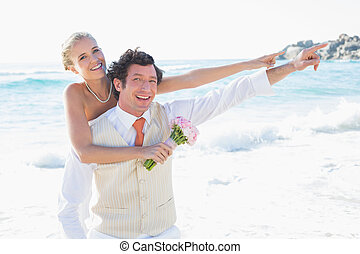 Newlyweds pointing to something smiling at camera at the...