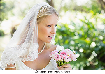 Happy bride in a veil holding her bouquet in the countryside