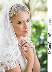 Smiling bride in a veil holding her hands to her chest in...