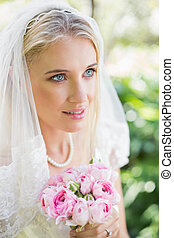 Happy bride wearing veil holding bouquet looking away