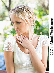Content blonde bride with hand on chest in the countryside
