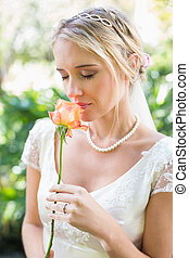 Smiling blonde bride in pearl necklace smelling rose in the...