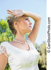 Pretty blonde bride holding arm to forehead on sunny day in...