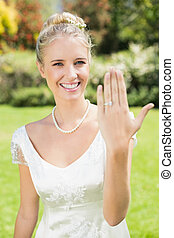 Happy bride showing her ring in the countryside