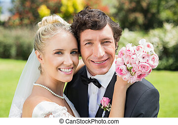 Attractive bride and groom hugging and smiling at camera in...