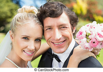 Attractive bride and groom smiling at camera in the...