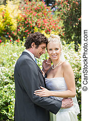 Romantic smiling newlyweds embracing looking at camera in...