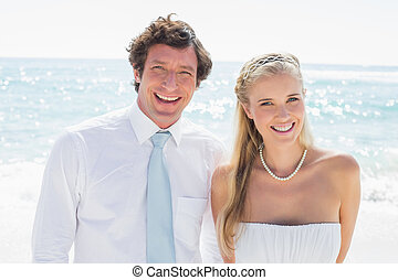 Romantic couple smiling at camera on their wedding day