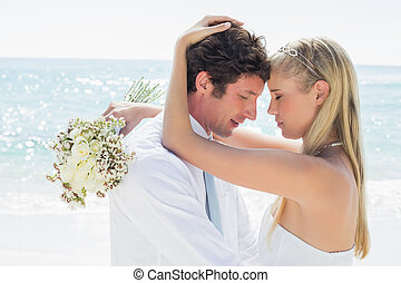 Romantic couple embracing on their wedding day at the beach