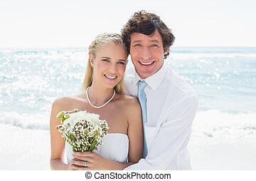 Romantic couple on their wedding day smiling at camera