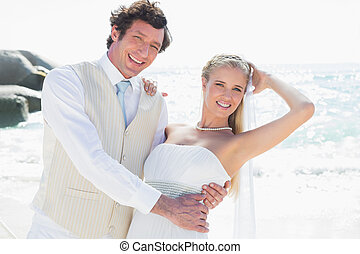 Groom holding his smiling new wife while dancing looking at...