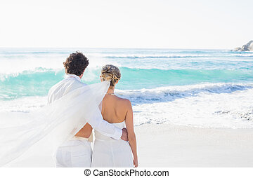 Newlyweds looking out to sea together at the beach