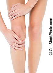 Close-up mid section of a young woman with knee pain over...