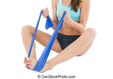 Fit woman exercising with a blue yoga belt - Low section of...