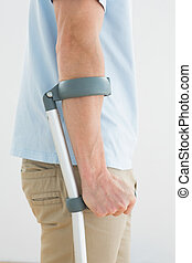 Close-up mid section of a man with crutch standing against...