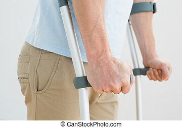 Close-up mid section of a man with crutches standing against...