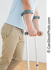 Side view mid section of a man with crutches standing...
