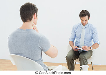 Well dressed male doctor in conversation with patient in the...