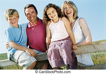 Family on fence outdoors smiling