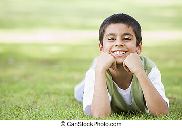 Young boy lying in grass outdoors in park smiling (selective focus)