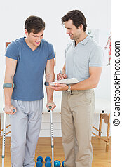Male therapist discussing reports with a disabled patient in...