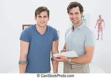 Smiling male therapist and disabled patient with reports