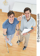 Male therapist gesturing thumbs up with disabled patient -...