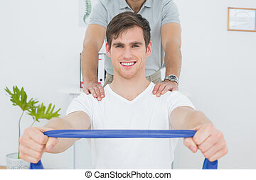 Man doing exercises with the help of therapist in office -...