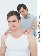 Male physiotherapist massaging a young mans shoulder over...