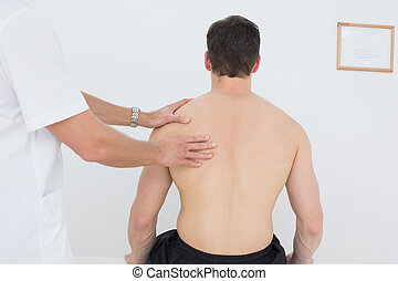 Shirtless man being massaged by a physiotherapist