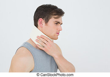 Side view of a young man wearing cervical collar over white...