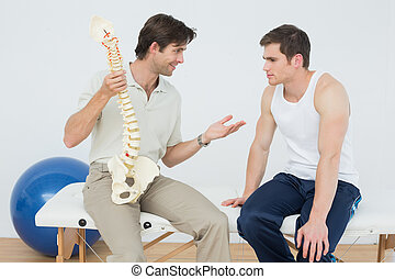 Friendly physiotherapist explaining the spine to a patient -...