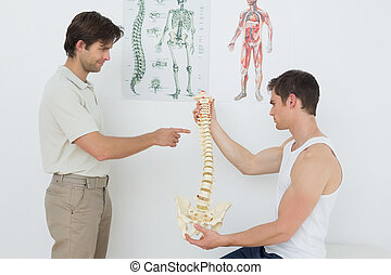 Physiotherapist showing patient something on skeleton model...