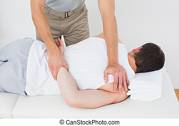 Male physiotherapist massaging patient