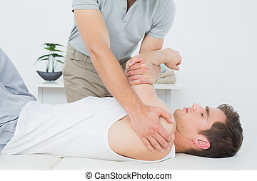 Male physiotherapist examining a mans hand - Male...