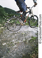 Man outdoors on trails jumping bicycle over puddles (selective focus)