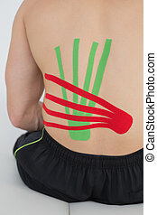 Shirtless man with red and green kinesio tapes on back -...