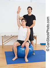Man on yoga ball while working with physical therapist