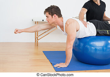 Physical therapist assisting young man with yoga ball in the...