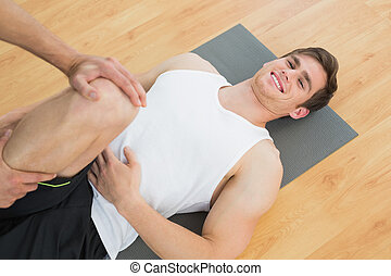 Physical therapist examining a smiling young mans leg