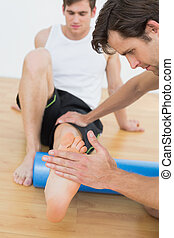 Physical therapist examining a young mans leg