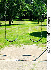 Two empty swings in park against trees and grass