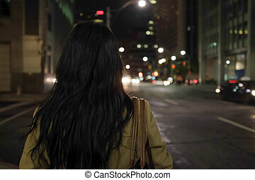 Woman standing at intersection - Woman standing at a street...