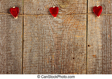 Clothes-peg in shape of heart on old wooden background