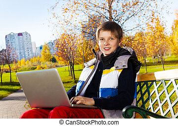 Boys learning with laptop outside